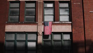 American Flag Against a Brick Building